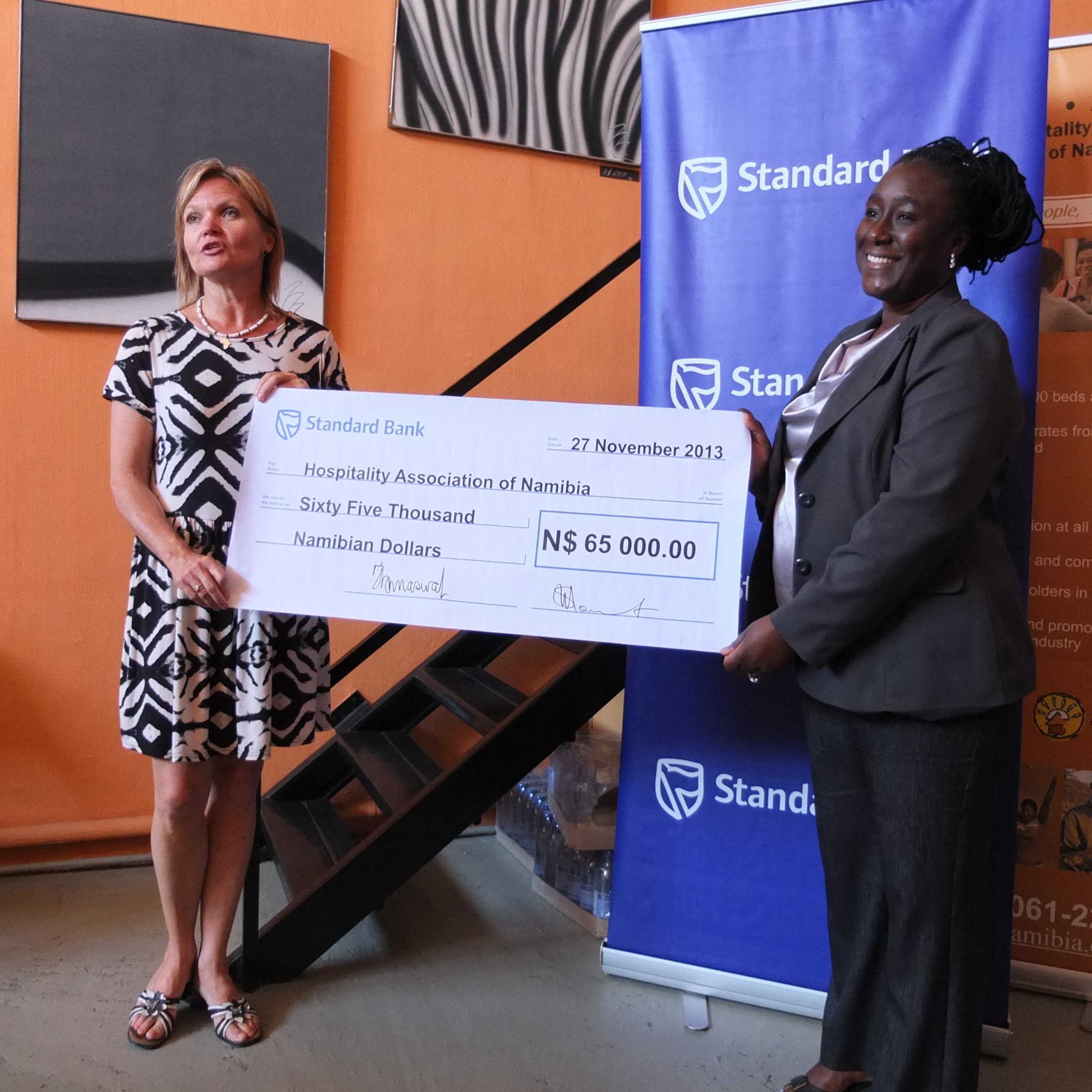 Surihe Gaomas-Guchu, the bank's PR & Communications Manager hands over the cheque to Gitta Paetzold.