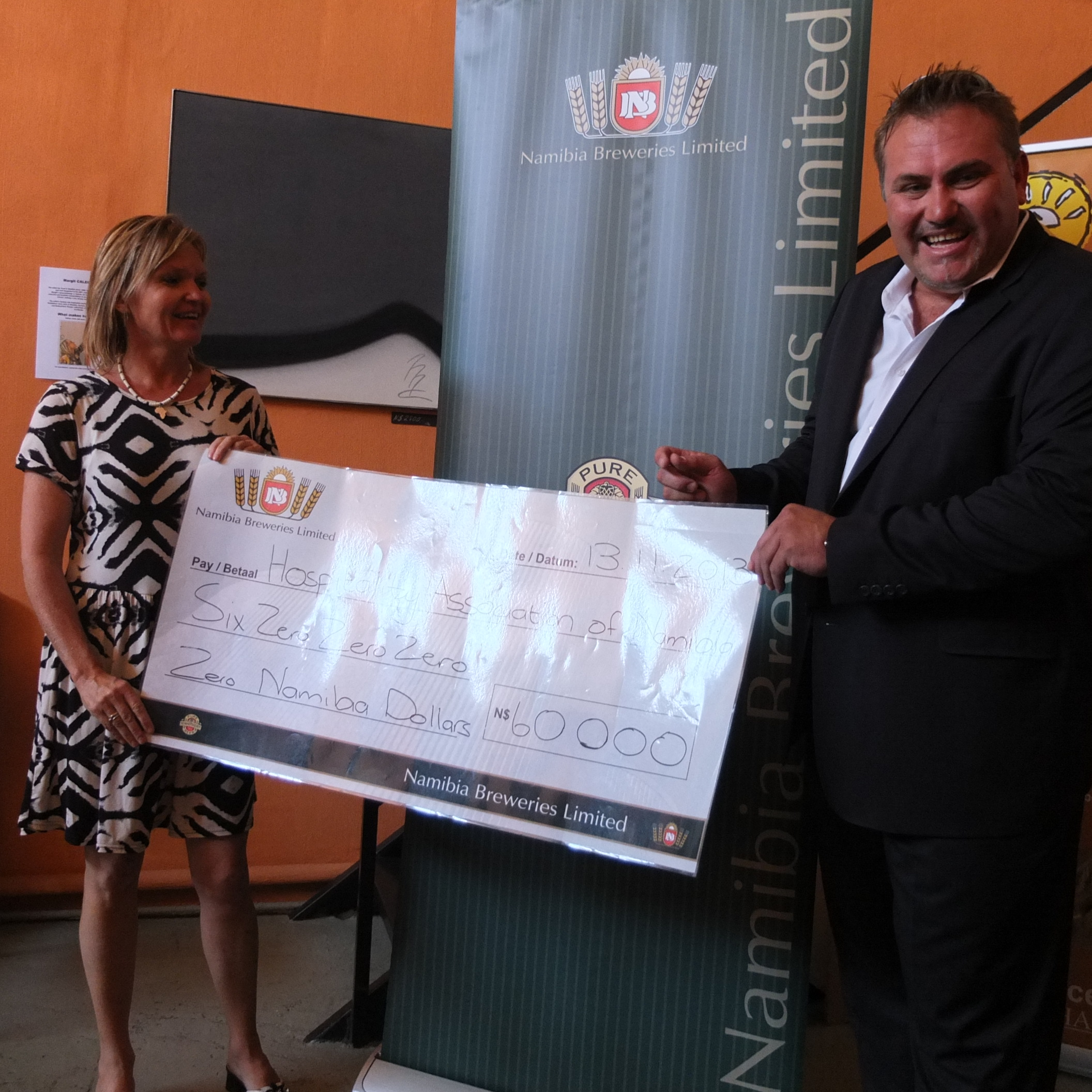 Wessie van der Westhuizen, Managing Director of Namibia Breweries Limited hands over the cheque