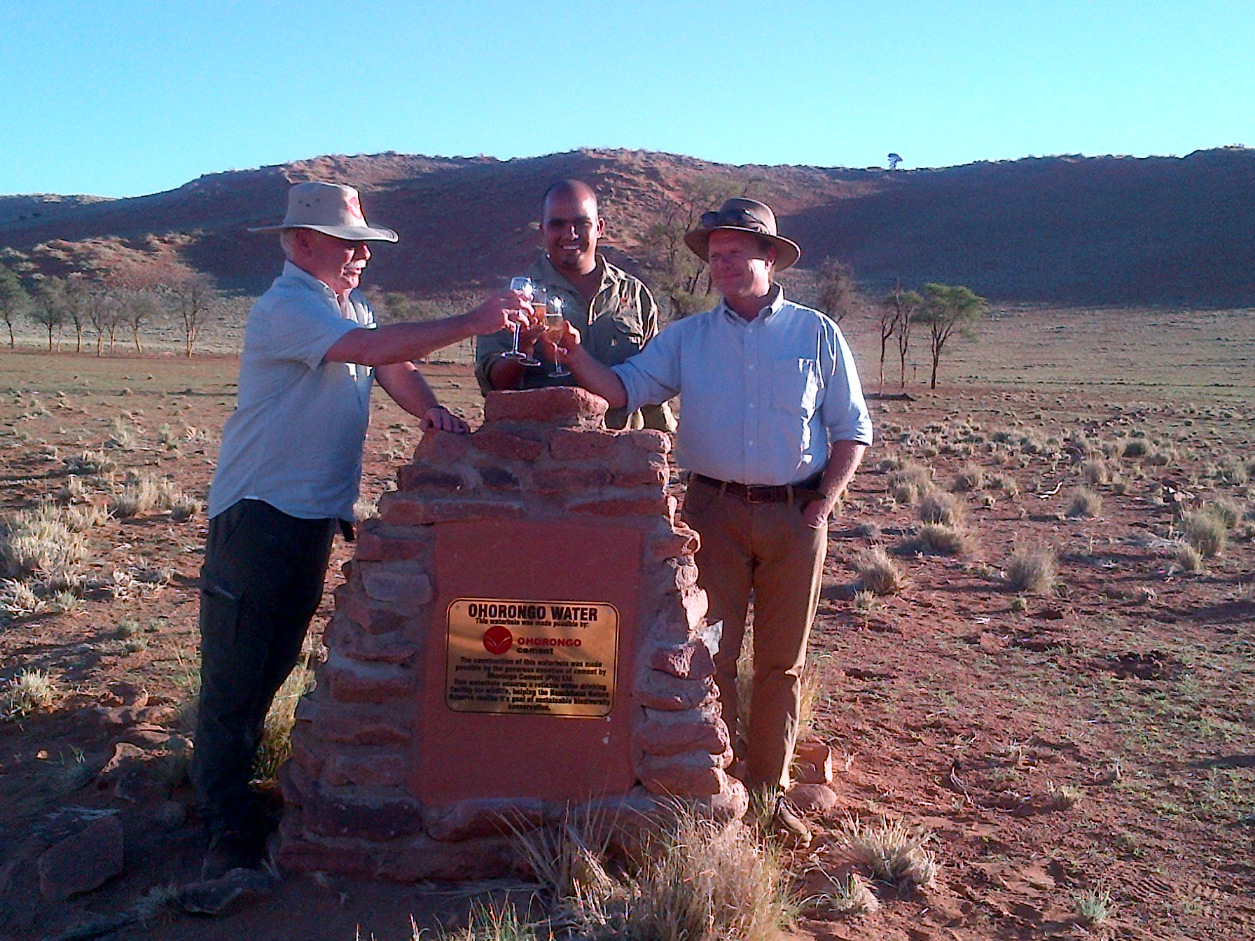 Mr Gerhard Hirth (CEO of Schwenk Zement KG), Quintin Hartung (Acting Control Warden of the NamibRand Nature Reserve) and Stephan Brueckner (MD of Wolwedans/NamibRand Nature Reserve) celebrated the new waterhole on the Reserve, proudly built with Ohorongo Cement.