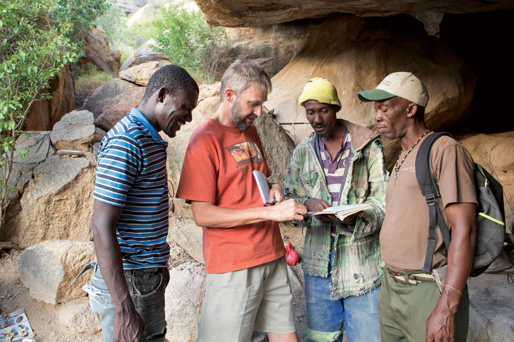 Guide-Jansen-(right)-listens-whiel-Arnold-shows-gem-specimens-from-Erong-in-a-book