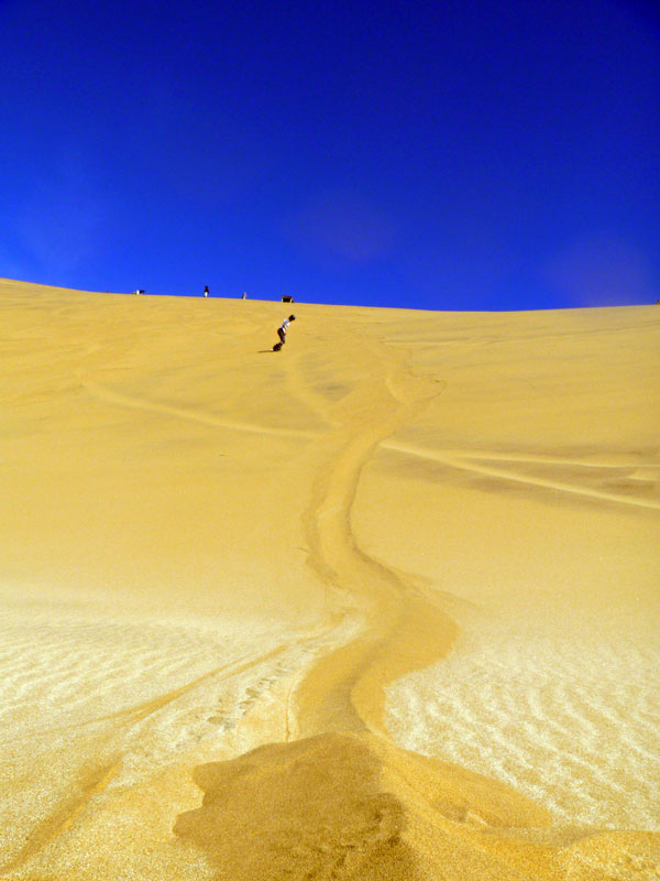 Surfing a dune. Namibia. Photo By Simon - The Nomadic Diaries